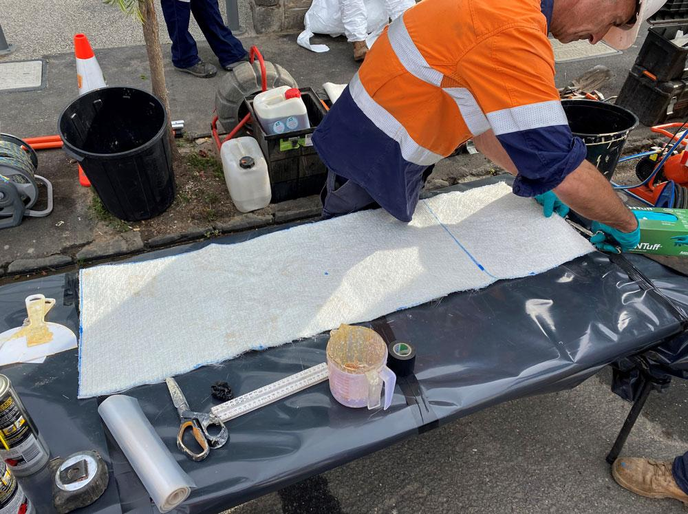 Trenchless fibreglass patch prep for a sewer pipe repair job.
